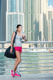 Workout. Athletic woman in sportswear holding bottle of water an Stock Image