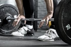 Workout with barbell. Barbell on the floor and the man's hands on it on the background of guy's legs in the black pants and white sneakers. Close-up horizontal royalty free stock photos