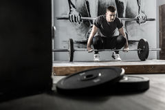 Workout with barbell in gym. Handsome guy with a beard prepares to raise up a barbell in the gym on the wall with picture background. He wears sportswear with Royalty Free Stock Image