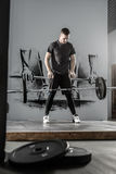 Workout with barbell in gym. Nice guy with a beard throws the barbell in the gym on the wall with picture background. He wears sportswear with the white sneakers Stock Photography