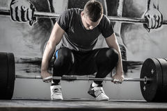 Workout with barbell in gym. Powerful guy with a beard prepares to raise up a barbell in the squat in the gym on the wall with picture background. He wears Stock Photography