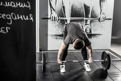 Workout with barbell in gym. Strong guy prepares to raise up a barbell in the gym on the wall with picture background. He wears sportswear with the white Stock Photography