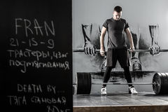Workout with barbell in gym. Young guy with a beard stands next to the barbell in the gym on the wall with picture background. He wears sportswear with the white Royalty Free Stock Photos