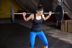 Workout of the day. Pretty girl doing some squats with a barbell in a gym Stock Photos