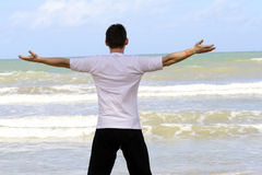 Workout exercises on the beach. Man doing breathing exercises on the beach Stock Photos