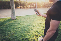 Workout fitness concept.Muscular handsome athlete checking training programm on smartphone application before workout. Session on city park in the sunny morning Stock Photos