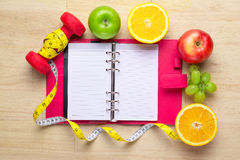 Workout and fitness dieting copy space diary. Healthy lifestyle concept. Apple, dumbbell, and measuring tape on rustic wooden tabl Royalty Free Stock Photography