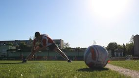 Workout of footballer before training. Guy flexing his muscles during the session stock footage