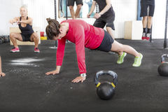 Workout group trains different exercises. A fitness group training push ups, hang ups and squat at a gym center Stock Photo