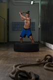 Workout At Gym With Hammer And Tractor Tire Stock Photo