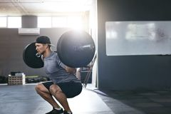 Workout At Gym. Sports Man Doing Squats With Barbell Row royalty free stock images