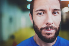 Workout indoor lifestyle concept.Portrait of young bearded man athlete standing in fitness gym on blurred background Royalty Free Stock Image