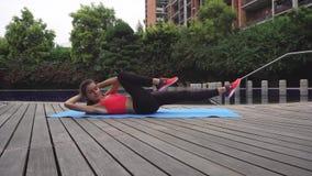 workout Jonge vrouw die oefening voor spieren van buikpers in openlucht doen stock video