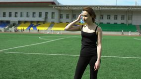 Workout on a lawn. Young fit woman is warming up on a lawn on a stadium stock footage