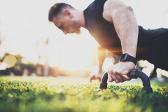 Workout lifestyle concept.Muscular athlete exercising push up outside in sunny park. Fit shirtless male fitness model in royalty free stock photo