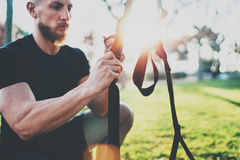Workout lifestyle concept.Muscular athlete preparing TRX for exercising outside at summer park.Great trx workout sunny royalty free stock images