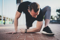 Workout lifestyle concept.Young man doing stretch exercises muscles before training.Muscular athlete exercising outside royalty free stock photo