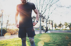 Workout lifestyle concept.Young man preparing muscles before training.Muscular athlete exercising outside in sunny park royalty free stock photography