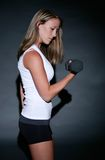 Workout look. Young woman wearing workout outfit curling a dumbbell Stock Photos
