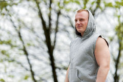 Workout man in hood resting. Outdoor. Stock Photo