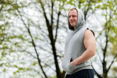 Workout man in hood resting. Outdoor. Stock Image
