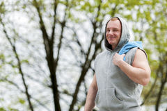 Workout man in hood resting. Outdoor. Stock Photos