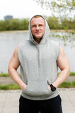 Workout man in hood resting by the river outdoor. Royalty Free Stock Photo