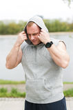 Workout man in hood resting by the river outdoor. Royalty Free Stock Images