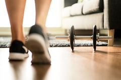 Workout motivation, fitness determination and exercising concept. Morning training in sunlight. Person with gym equipment at home. Sneakers and dumbbell royalty free stock photo