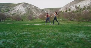 Workout at nature two women running through a green field and Mountain landscape in a perfect summer day , take the. Video large view stock footage