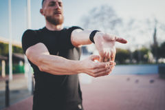 Workout outdoor lifestyle concept.Young man stretching his arm muscles before training.Bearded Muscular athlete royalty free stock image