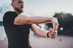 Workout outdoor lifestyle concept.Young man stretching his arm muscles before training.Young Muscular athlete exercising Royalty Free Stock Photography