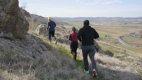 Workout outdoors. Two men and woman jogging over rough terrain in autumn or spring. Trail running. Workout outdoors. Two men and woman jogging over rough stock video footage