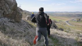 Workout outdoors. Two men and woman jogging in slow motion over rough terrain in autumn or spring. Trail running. Workout outdoors. Two men and woman jogging in stock footage