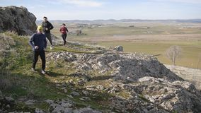 Workout outdoors. Two men and woman jogging in slow motion over rough terrain in autumn or spring. Trail running. Workout outdoors. Two men and woman jogging in stock video