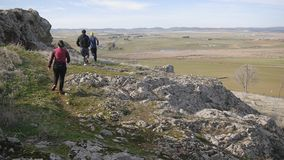 Workout outdoors. Two men and woman run over rough terrain in autumn or spring. Trail running. Workout outdoors. Two men and woman run over rough terrain in stock footage
