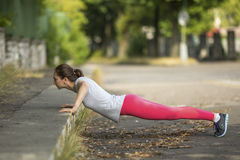 Workout in a Park. Young sporty woman doing push-ups in park in sunshine on beautiful summer day. Stock Image