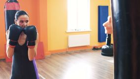 A woman in boxing gloves beats punching bag in Gym with personal coach. Workout with instructor in a fitness club stock footage
