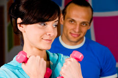 Workout with personal trainer. Smiling young woman at the health club with her personal trainer Stock Images