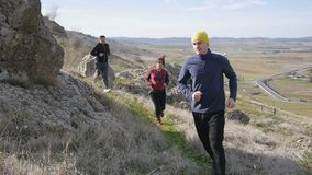 Workout with personal trainer outdoors. Two men and woman jogging over rough terrain in autumn or spring. Trail running. Workout with personal trainer outdoors stock video