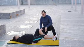 Workout with personal trainer outdoors. Woman lies on yellow mat doing air cycling. The coach correcting proper stock video