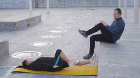 Workout with personal trainer outdoors. Woman lies on yellow mat doing air cycling. The coach demonstrating the proper stock video footage
