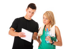 Workout plan. A picture of a young couple discussing workout plan over white background Stock Image