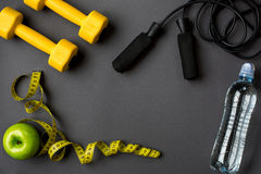 Workout plan with fitness food and equipment on gray background, top view
