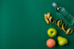 Workout plan with fitness food and equipment on green background, top view