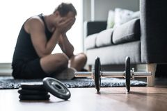 Workout problem, stress in fitness or too much training. Sad or tired man having trouble with overtraining. Exhausted and unhappy athlete with depression royalty free stock image