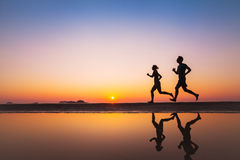 Workout, silhouettes of two runners on the beach. At sunset, sport and healthy lifestyle background Royalty Free Stock Photos