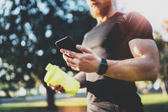 Workout smart fitness concept.Young Muscular athlete checking training programm on smartphone application after perfect. Workout session at sunny morning Royalty Free Stock Image