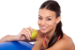 Workout snack. Cropped shot of a young attractive woman sitting next to her fitness ball and eating an apple Royalty Free Stock Image