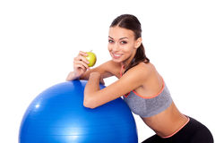 Workout snack. Portrait of a young woman sitting next to her fitness ball and eating an apple Stock Photos
